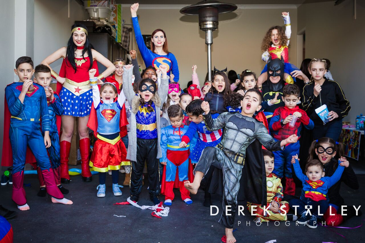 Happy children and Superheroes at a Superhero themed birthday party