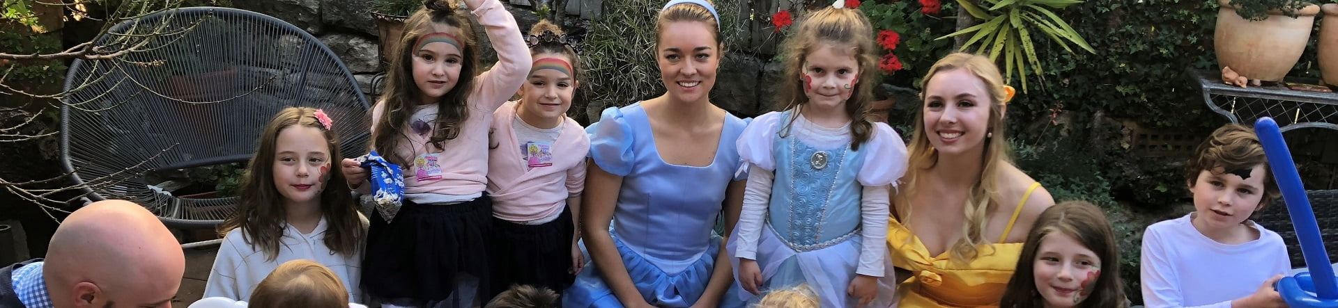 image of princess themed birthday party entertainers Belle and Cinderella with smiling children