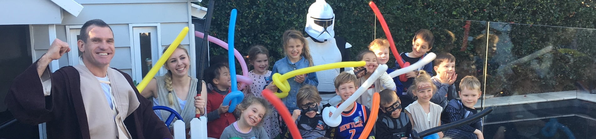 Image of Star Wars themed Jedi birthday party entertainers with smiling children holding balloon lightsabres